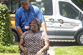Virginia Premier employee helping woman in wheelchair