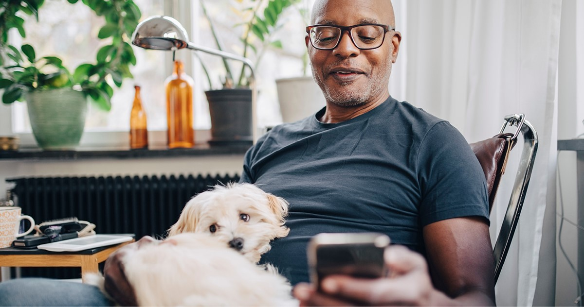 Man with dog on lap looking at mobile phone