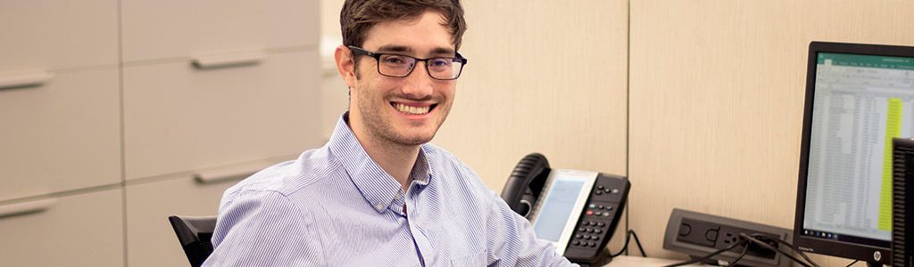 man with glasses smiling sitting a desk