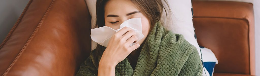 woman wrapped in blanket on couch blowing her nose