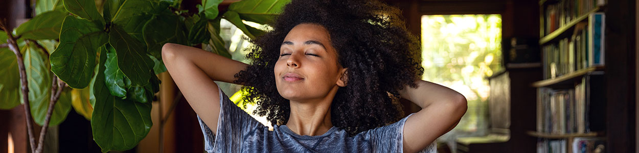 woman relaxing with eyes closed and hands behind her head