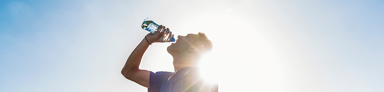 man drinking water in sun